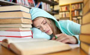 people, education, session, exams and school concept - tired student girl or young woman with books sleeping in library; Shutterstock ID 292918232; PO: Brandon for trending